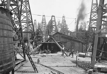 Two_men_standing_near_a_wooden_shed_in_the_midst_of_dozens_of_oil_derricks_in_a_Los_Angeles_oil_field_1